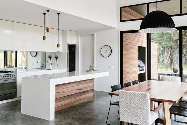 10. Phòng bếp tối giản màu trắng tinh tế và góc ăn hiện đại được kết nối bằng màu sắc và những chiếc đèn treo.