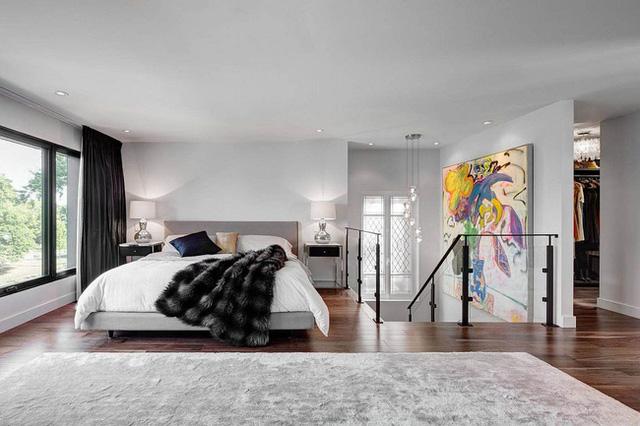 Theo chân cầu thang lên tầng hai là một bức tranh mang phong cách trừu tượng, cổ điển cỡ lớn. Nơi đây chính là không gian phòng ngủ. Phòng ngủ trông khá hiện đại và ấm áp với thảm và chăn lông dày dặn.