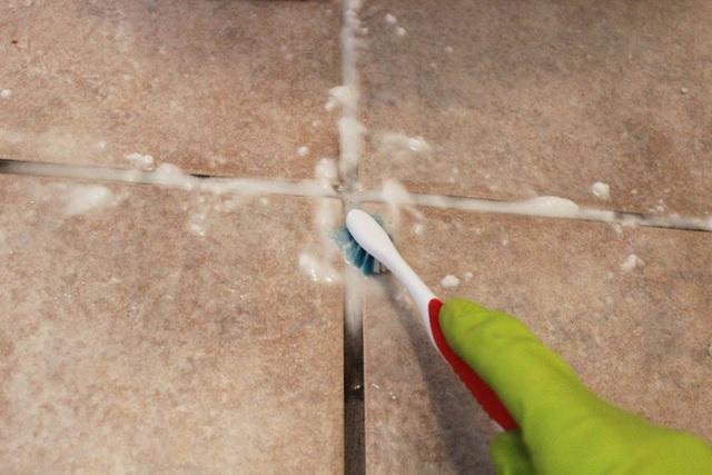 Dùng bàn chải để chà dung dịch giấm lên trên khu vực xi măng. Khi bạn thấy hỗn hợp chuyển màu tối là được.