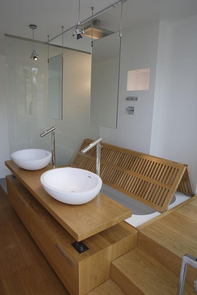 Một chiếc bồn tắm chìm đơn giản cũng đủ làm phòng tắm này nổi bật nhờ thiết kế độc đáo của các kiến trúc sư A-OMA với cánh cửa chớp đặc biệt. Bồn tắm được bao bọc bởi gỗ, có cầu thang đi xuống, kèm hai bồn với kiểu dáng đẹp và rất phong cách.