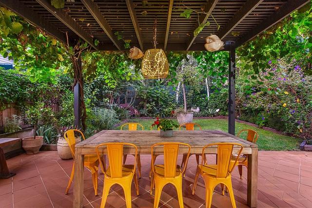 Bàn bằng gỗ và ghế màu vàng sáng để ăn ngoài trời trên sân hiên.