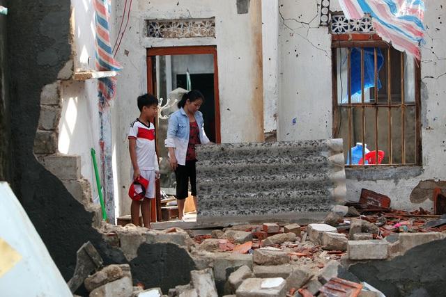 Hai mẹ con đứng nhìn ngôi nhà tan hoang sau bão. Du chịu thiệt hại nặng về nhà cửa, tài sản, hai thôn Hải Bắc và Hải Nam không có thiệt hại về người do người dân đã được sơ tán tới những nơi tránh trú an toàn trước khi bão đổ bộ.