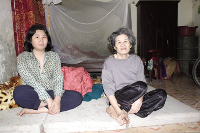 Bà Nở và cô con gái út là Bích - đang phải điều trị bệnh tâm thần tại nhà. Ảnh: Minh Lý