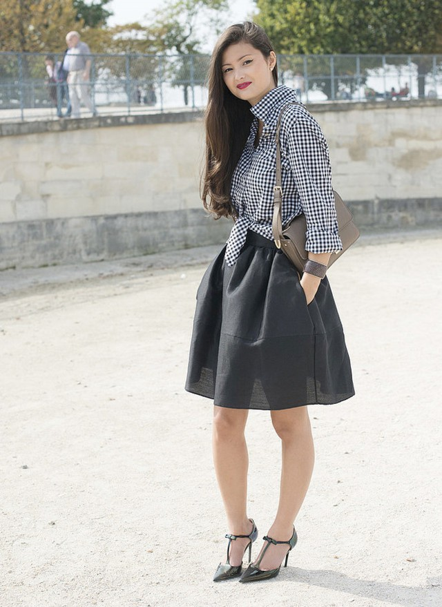 Set đồ kinh điển là chân váy đen và áo sơ mi ca rô sẽ trở nên khác lạ. Thay vì đóng thùng theo cách truyền thống, bạn hãy buộc 2 vạt trước của sơ mi lại