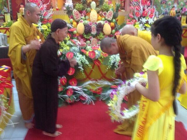 Đại đức Thích Thanh Phương dâng lên mẹ một vòng hoa màu vàng tại lễ Vu lan báo hiếu. Ảnh: T.G