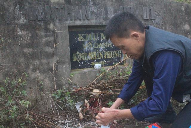 Ông Thìn sửa sang lại lọ cắm hương trước tấm bia khu mộ vô danh do lâu ngày không ai lui tới. Ảnh: H.Phương