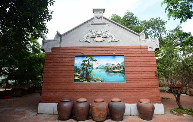 Phía sau ngôi nhà là bức phù điêu nổi với cảnh non nước hữu tình do các thợ Hà Tây đắp bằng tay.
