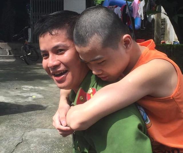 Nụ cười của thiếu uý Chu Ngọc Hơn cõng em Hưng bị tàn tật trên lưng khiến nhiều người cảm động. Ảnh: T.Lê