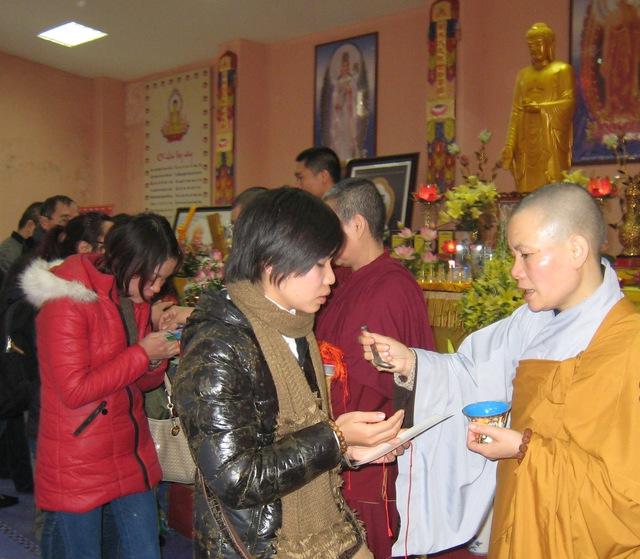 Lộc Phật thơm tho, một tí cũng là lộc. Các phật tử xếp hàng xin lộc ở chùa. Ảnh T. G