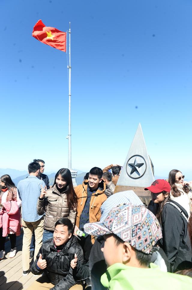 Du khách thích thú ngắm cột cờ Tổ quốc với 4 góc phù điêu được thượng cờ hồi đầu.