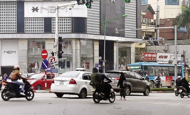 Ngay cả khi đèn đỏ, người đi bộ vẫn cố lạng lách qua đầu các phương tiện để sang đường. Ảnh:K.O