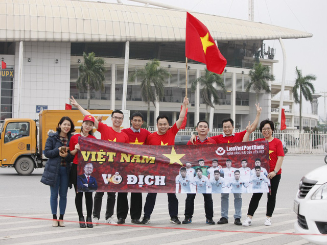 Một nhóm nhân viên ngân hàng mê bóng đá chụp ảnh cùng băng rôn khẩu hiệu trước sân vận động Mỹ Đình.