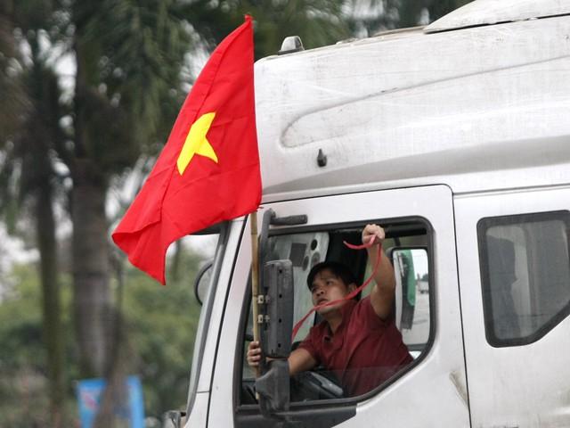 Một tài xế xe tải treo lá cờ lên cabin.