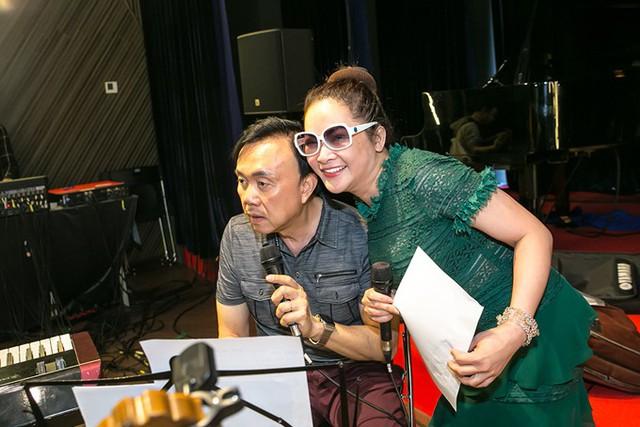 Nữ ca sĩ thoải mái tạo dáng trước ống kính bên cạnh Chí Tài chăm chú nhìn bản nhạc.