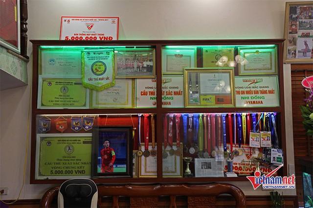 Trên tường phòng khách, bố mẹ tiền vệ Quang Hải đóng 1 tủ kệ gỗ, trưng bày các huy chương, giải thưởng cũng như các bài báo viết về con trai mình.