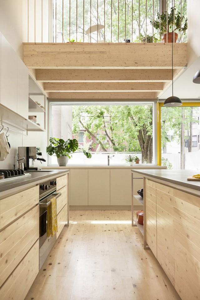 Hệ tủ bếp gỗ sáng màu với bàn bếp inox sáng, hiện đại và sạch sẽ.