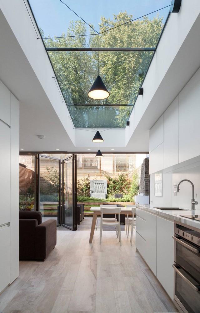 Cửa sổ trời bằng phẳng phục vụ toàn bộ chiều dài của không gian nhà bếp, phòng ăn, sảnh phòng khách hiện đại. Đèn mặt dây chuyền được rải rác trên kính, khi đêm xuống tạo ánh sáng lung linh.