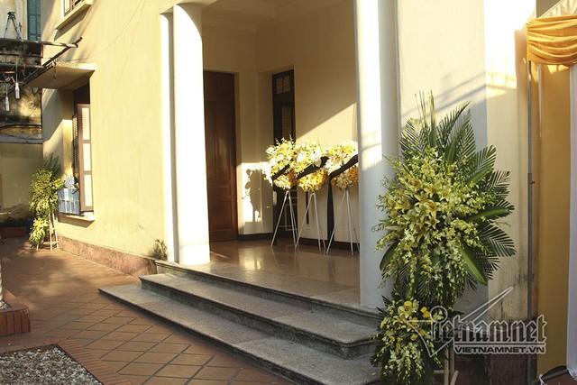 Không gian tĩnh lặng với nắng vàng, vòng hoa Bên trong chính giữa nhà, bàn thờ cùng di ảnh ông được đặt trang trọng