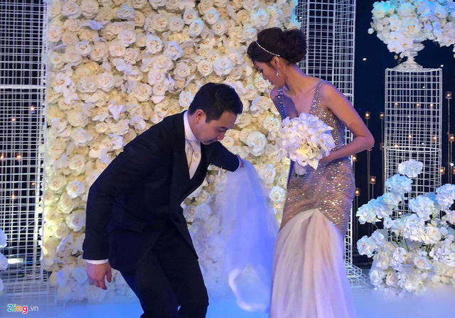 Lan Khuê và chú rể cười hạnh phúc, rạng rỡ đón tiếp khách mời. Cả hai tay trong tay và trao nhau ánh nhìn say đắm. Thỉnh thoảng, chú rể còn cúi xuống, chỉnh váy giúp cô dâu di chuyển.