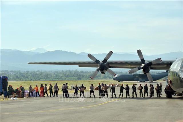 Binh sĩ và cảnh sát Indonesia chuyển hàng cứu trợ từ máy bay ở Palu, tỉnh Trung Sulawesi, Indonesia ngày 6/10/2018. Ảnh: AFP/TTXVN