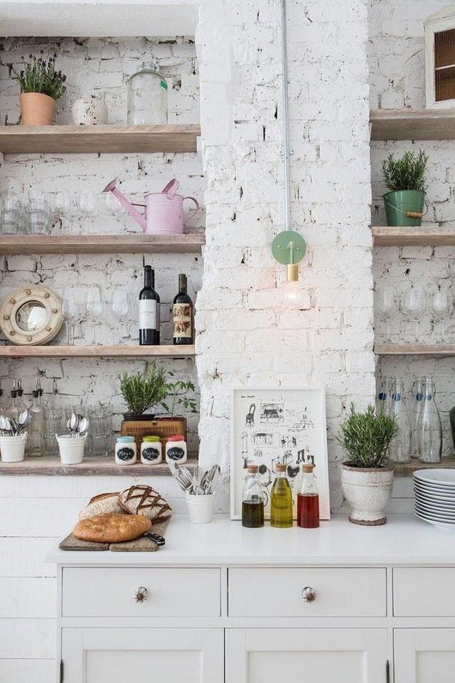 Sử dụng sơn trắng để sơn toàn bộ gạch trần trên tường trước khi lắp đặt kệ gỗ cũng là cách mang đến một không gian nấu nướng tinh tế và mộc mạc.