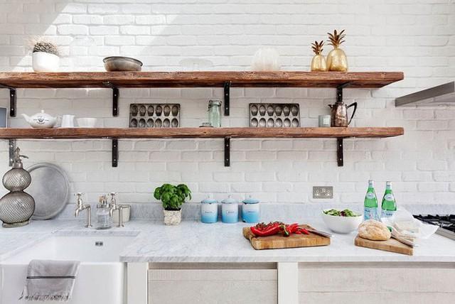 Nhà bếp sử dụng toàn bộ màu trắng làm tông nền sẽ được mở rộng và sâu hơn nhờ thiết kế kệ gỗ gắn tường.