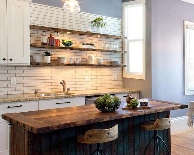 Một chiếc đảo bếp bằng gỗ thô mộc sẽ giúp không gian nấu nướng đươc kết hợp ăn ý hơn với kệ gỗ. Yếu tố không thể thiếu cho không gian nấu nướng này chính là đèn chiếu sáng màu vàng ấm áp.