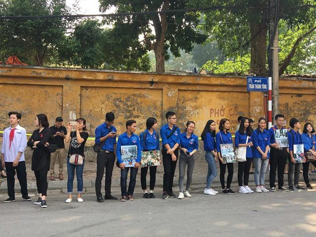 Đội tình nguyện viên đứng hai bên phố trước cửa Nhà tang lễ Quốc gia. Ảnh: Kim Oanh