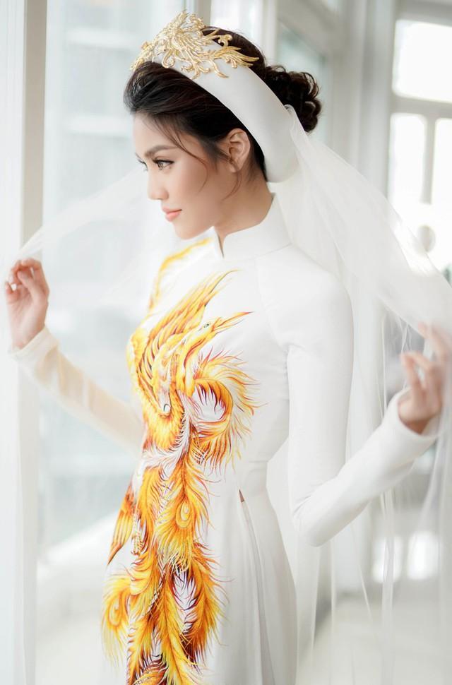 Trong ngày ăn hỏi, khác hoàn toàn với các cô dâu khác, Lan Khuê chọn riêng cho mình thiết kế áo dài trắng in hình cánh phượng quyền quý. Và đương nhiên tông trang điểm hợp với thiết kế áo dài cao sang này không gì khác là gam màu cam sáng nền nã. Khá nhiều người tinh ý nhận ra, bình thường rất hay chuộng son trầm đậm màu, nhưng đến ngày cưới Lan Khuê dịu dàng e ấp hơn hẳn với tông cam hiền dịu.