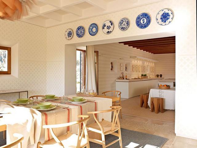 12. Phòng ăn nối liền khu vực nấu nướng. Treo những chiếc đĩa trang trí làm không gian ăn uống gợi nên sắc màu rõ rệt.