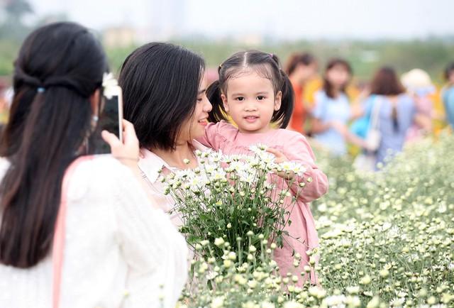 Dù tiết trời Hà Nội ngày cuối tuần khá nắng nhưng cũng không quản bước chân của những người yêu loài hoa này, trong số đó nhiều bà mẹ trẻ đã không cưỡng lại được vẻ đẹp nên đã cho con em mình đến những vườn cúc.