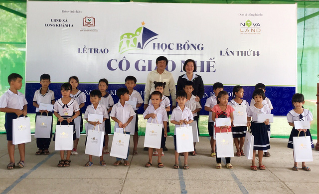 Đại diện Tập đoàn Novaland và lãnh đạo địa phương trao học bổng đến các em học sinh hiếu học.