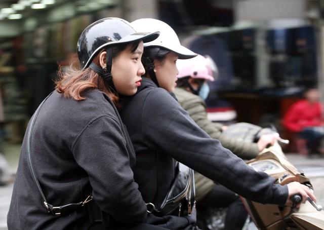Hai người phụ nữ nép vào nhau khi di chuyển trên đường.