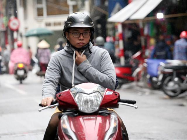 Chàng trai trẻ phải dùng tay giữ cổ áo khi di chuyển trên đường.