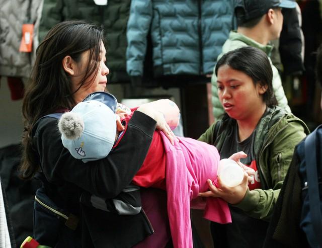 Một du khách ngoại quốc đi du lịch tại Việt Nam mang theo con nhỏ chỉ vài tháng tuổi đã được 1 người dân trên phố Hàng Đào quấn lại chiếc chăn giúp bé bớt lạnh.
