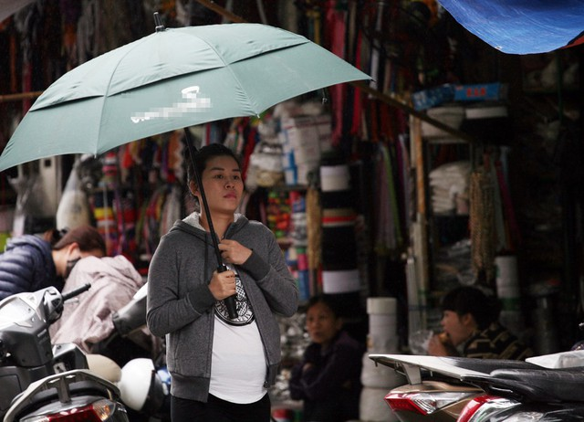 Một phụ nữ mang bầu vội lấy tay che lại cổ trước cơn gió lạnh.