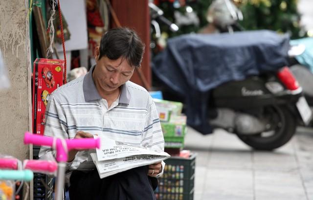 Thưởng thức ly trà nóng và đọc thông tin từ một tờ báo vừa ra sáng nay là cách người đàn ông thường làm trong ngày gió lạnh.