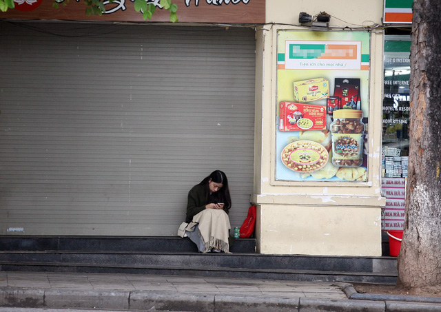 Một cô gái ngồi co ro ở góc vỉa hè trước một tiệm ăn nhanh chưa kịp mở cửa.