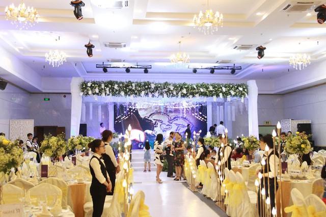 Lối đi dẫn vào sân khấu chính trong phòng tiệc được thắp sáng bởi dàn đèn có độ cao thấp khác nhau, tạo độ lung linh cho không gian.         Uyên ương chọn bàn tròn và ghế banquet giúp khách mời dễ dàng theo dõi những diễn biến, hoạt động diễn ra trên sân khấu.         Êkíp đã kết hoa tươi và những dải dây bắt sáng trên trần nhà để tạo điểm nhấn cho không gian, giúp tăng vẻ lãng mạn.         Mỗi bàn tiệc đều được trang trí bởi một bình hoa tươi gồm hoa hồng và các loài hoa phụ.         Từng chiếc ghế đều được làm điệu bởi dải nơ vàng - sắc màu chủ đạo của tiệc cưới.         Uyên ương chọn bánh cưới 3 tầng màu trắng và được trang trí bởi hoa lan hồ điệp.         Tại đám cưới, Hoa hậu Thu Thảo mời một số gương mặt nổi tiếng trong làng giải trí tới dự như ca sĩ Nguyên Vũ (phải) và siêu mẫu Nam Phong (trái)... Đến ngày 26/11, cô dâu chú rể tổ chức lễ thành hôn tại Long Xuyên, An Giang.  Theo Ngôi sao