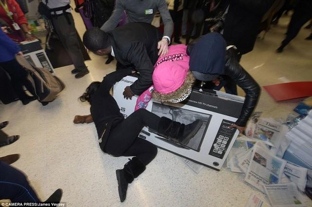 Một phụ nữ cố gắng nằm đè lên chiếc ti vi sau khi cãi nhau tranh giành chiếc ti vi này với những khách hàng khác tại 1 cửa hàng Asda ở Wembley.