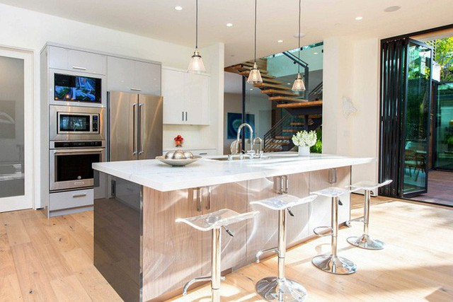 Tận dụng nơi bồn rửa, chủ nhà khéo léo lắp mặt bàn rộng, có thể ngồi như ở quầy bar.