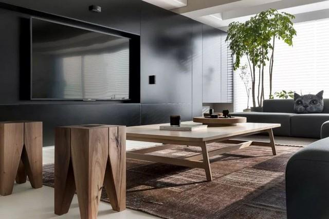 Bức tường phía trước sofa là nơi đặt tủ âm tường và tivi. Không sử dụng kệ như cách làm thông thường, toàn bộ bức tường màu đen với các ngăn tủ gọn nhẹ, tivi đặt ở vị trí trung tâm đủ để không gian sống thêm nổi bật cá tính.