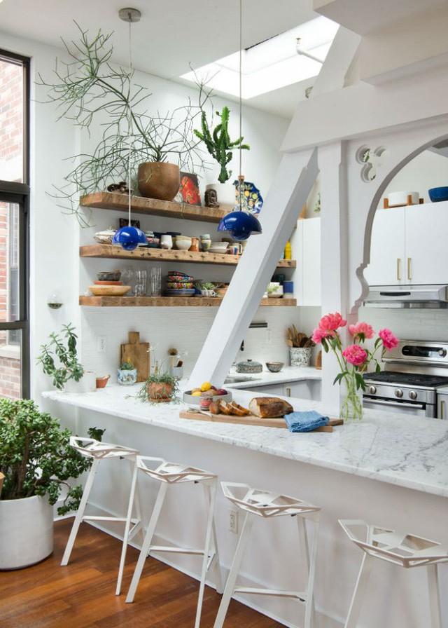 Không gian nấu nướng có diện tích nhỏ, nhưng không vì thế mà mọi người có cảm giác chật chội và ngột ngạt khi sử dụng. Ngoài việc lắp đặt cửa sổ kính để mang thật nhiều ánh sáng tự nhiên vào nhà, căn bếp còn được sơn toàn bộ với màu trắng tinh khôi. Tủ bếp chọn màu trắng cùng tông với màu nền, vừa giúp bếp gọn gàng vừa tăng thêm không gian lưu trữ.