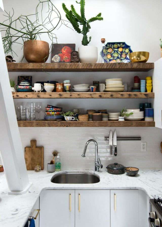 Vì bếp nhỏ, chủ nhân của nó chỉ lắp đặt hệ thống tủ phía dưới bàn chuẩn bị đồ ăn và một phần của bức tường. Góc tường còn lại được bố trí lắp đặt kệ gỗ, gam màu thân quen, gần gũi nhưng cũng không kém phần quyến rũ, ngọt ngào.