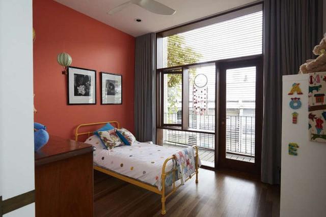 Phòng ngủ của con được đặt bên cạnh với khung cửa nhìn ra phía ngoài mặt tiền. Không gian đẹp sinh động với những gam màu táo bạo như cam, đen, nâu… Màu trắng của chăn ga được xem là màu nối để tăng thêm sự liên kết hài hòa với toàn bộ căn phòng.