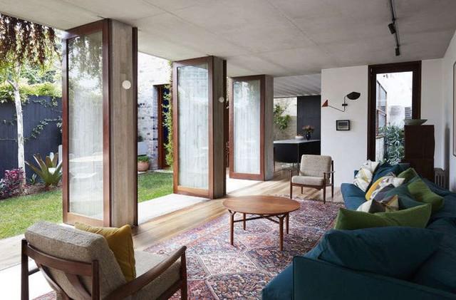 Thay vì thiết kế hai tầng như phần nhà gần mặt tiền, nhà nối phía sau được thiết kế mái bằng với các cánh cửa mở rộng ra khoảng hiên và thảm cỏ. Không gian bên trong được thiết kế đơn giản với sofa màu xanh đậm làm màu nhấn, thảm họa tiết Ấn Độ trung hòa, kết nối với màu sắc thiên nhiên bên ngoài.