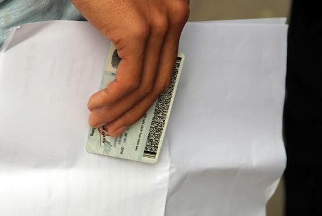 Người hâm mộ cầm sẵn những giấy tờ trước khi tiến vào khu vực nhận vé.