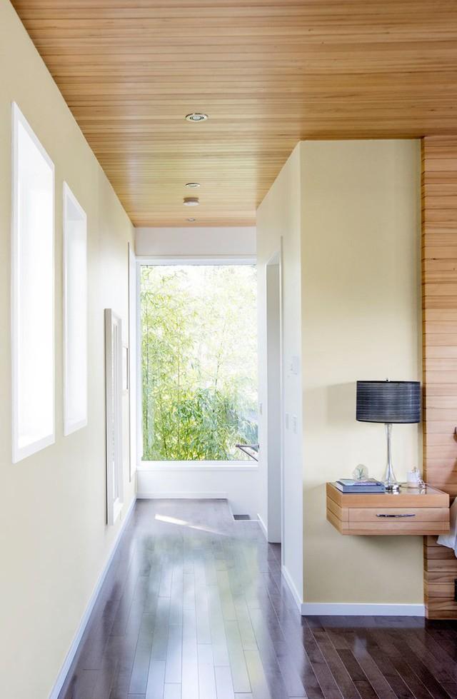 Trở vào trong, cầu thang dẫn lên phòng ngủ được ốp gỗ tối màu - tương phản với gỗ ốp sáng màu trên trần nhà.