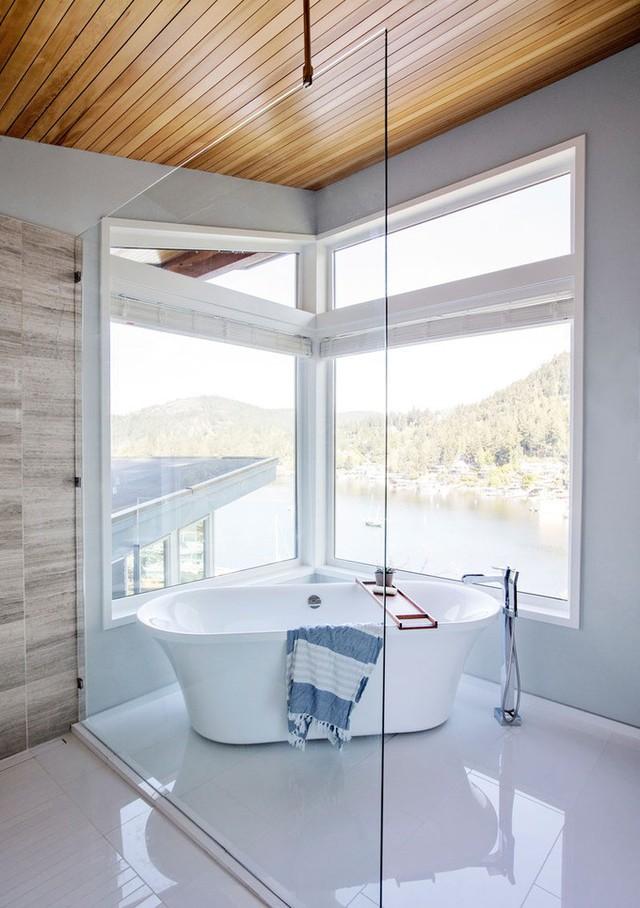 Bồn ngâm trong phòng tắm chính như nổi trên mặt biển nhờ bốn mặt tường kính và toàn bộ nội thất màu trắng tinh.