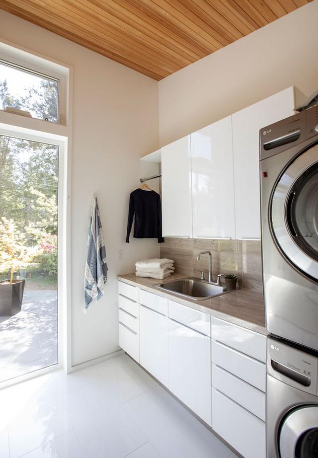 Cách đó vài bước, khu vực giặt ủi được trang bị tiện nghi với tủ đựng đồ bóng loáng, hệ thống máy giặt hiện đại, máy sấy...